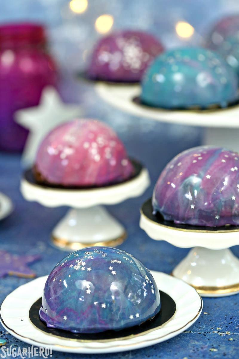Galaxy Mousse Cakes - Mini Mousse Galaxy Cakes displayed on mini cake stands. | From SugarHero.com