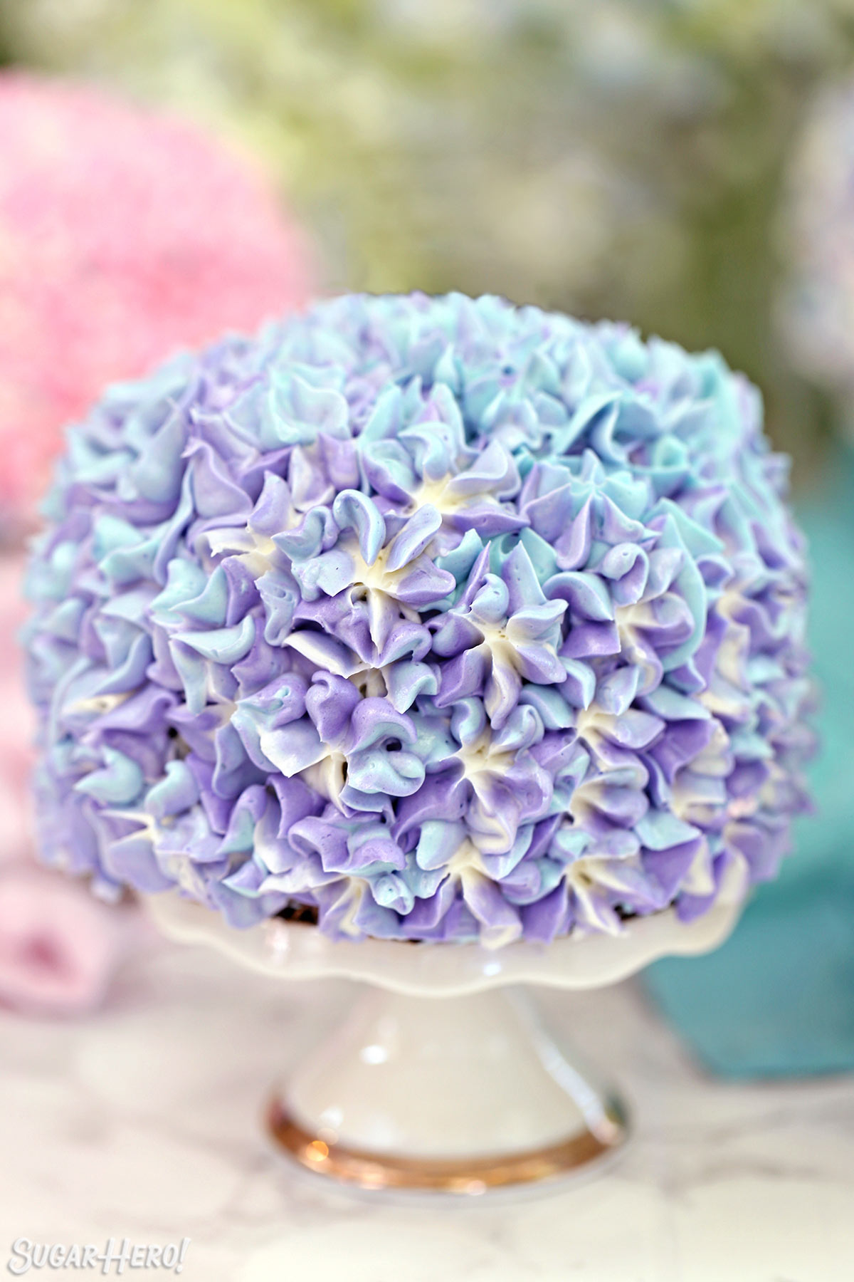 Hydrangea Cakes - A close up shot of a mini cake displayed on a stand. | From SugarHero.com