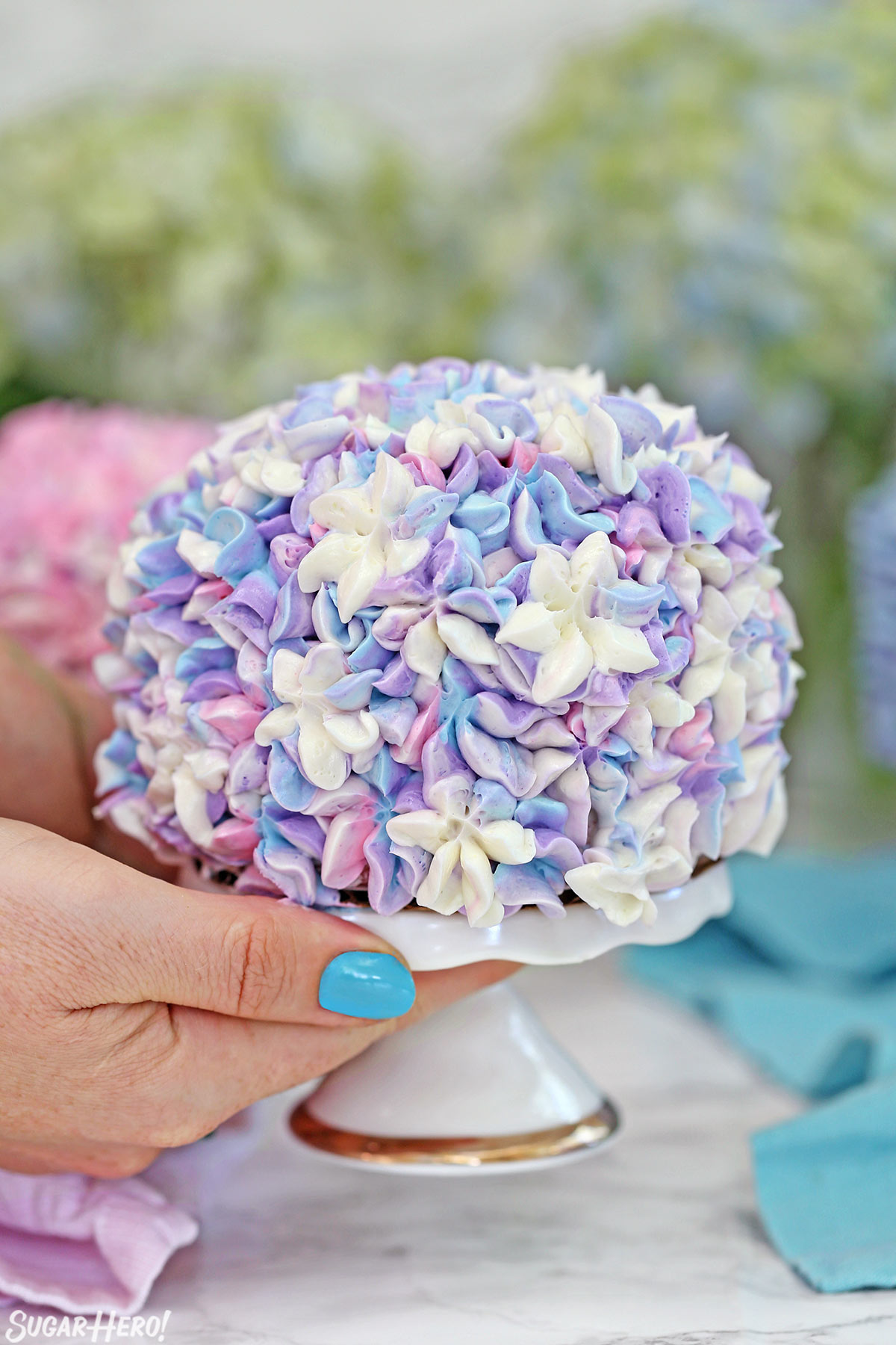 Hydrangea Cakes - A cake displayed on a cake stand. Covered in colorful flowers, to look like a hydrangea. | From SugarHero.com