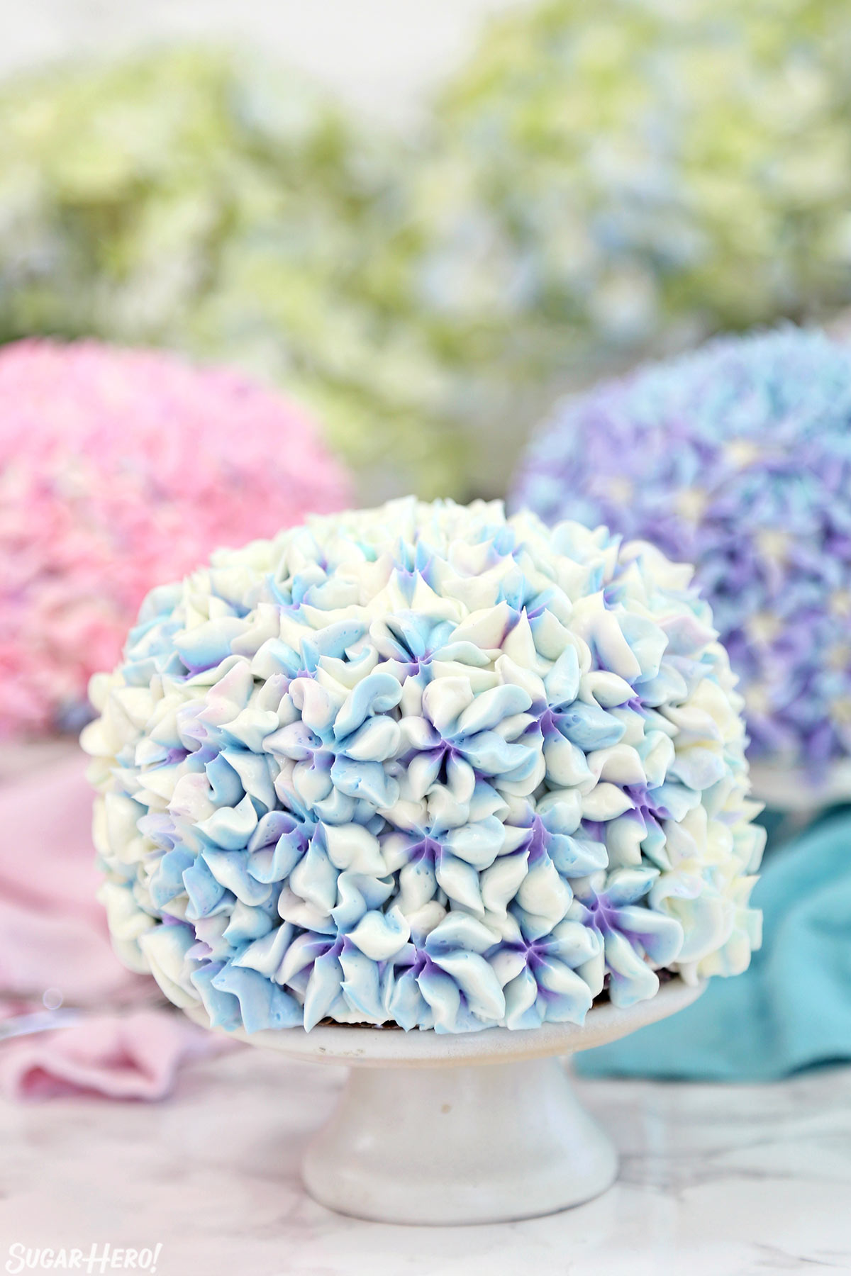 Hydrangea Cakes - A close up shot of a cake on a cake stand with blurred ones in the back. | From SugarHero.com