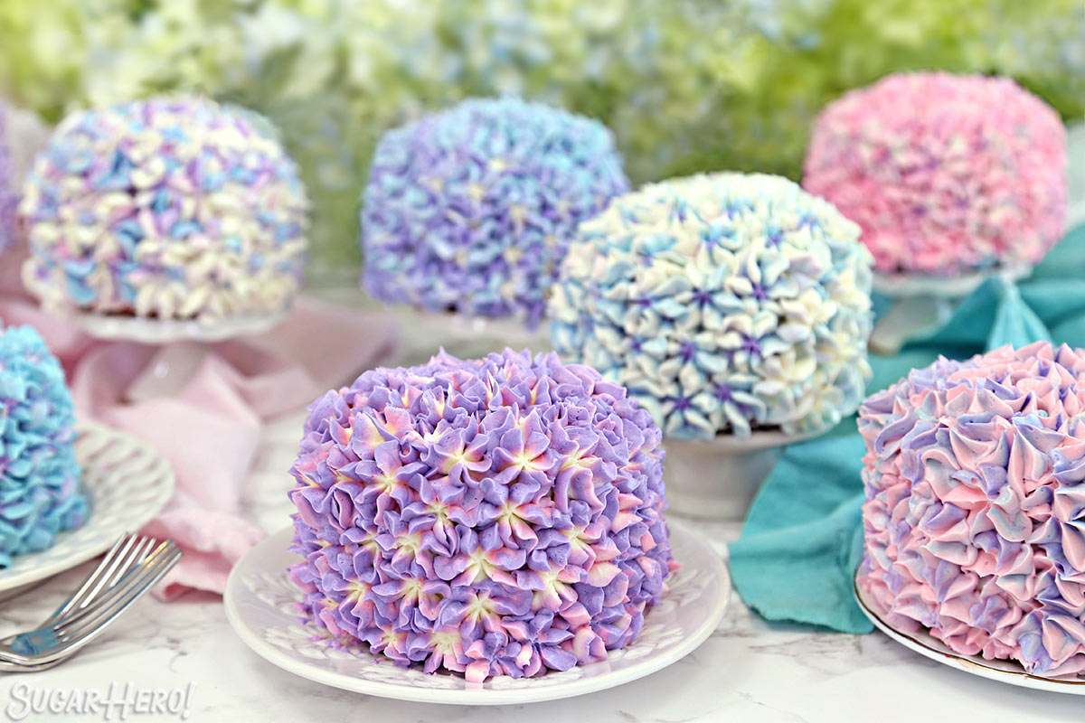 Hydrangea Cakes - Eight mini cakes displayed on plates and cake stands. | From SugarHero.com