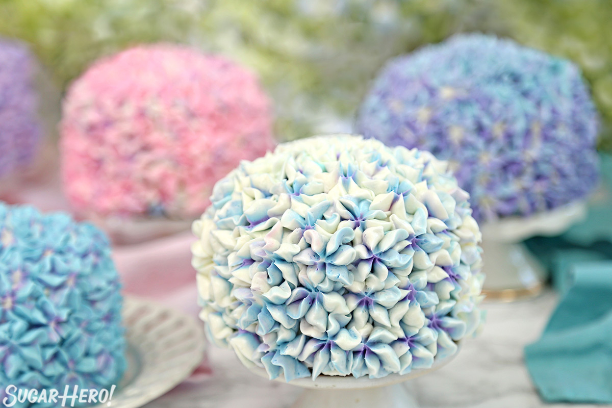 Hydrangea Cakes - A close up on one cake with others cakes blurred in the back, showing all the multi colored cakes. | From SugarHero.com