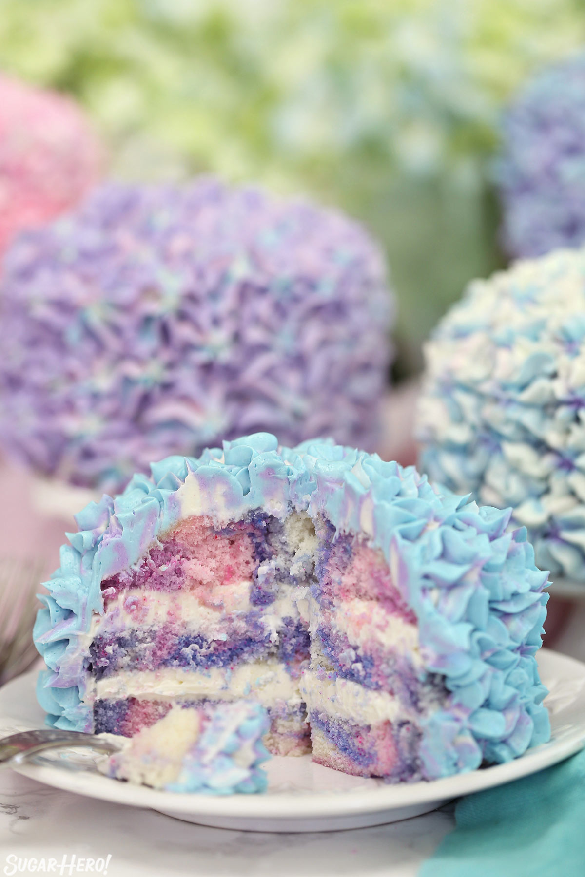 Hydrangea Cakes - A cake with bites take out showing the colorful inside. | From SugarHero.com