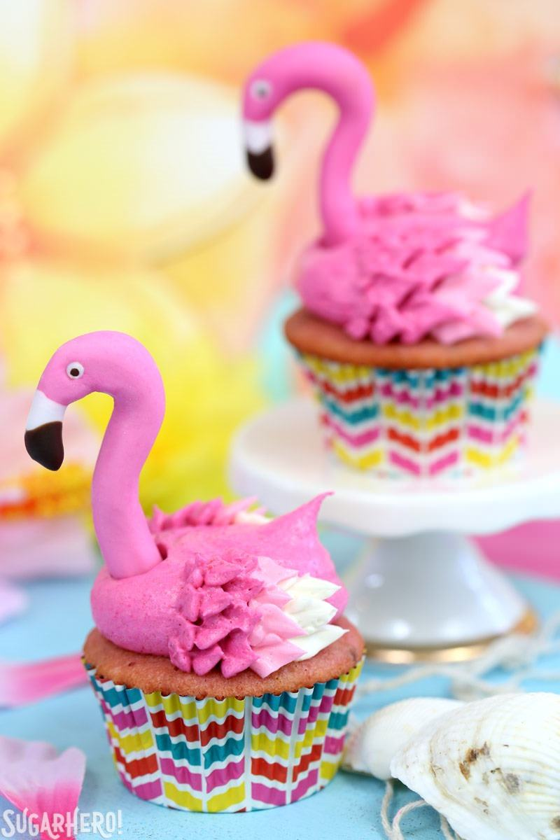 Two Pink Lemonade Flamingo Cupcakes with Fondant Flamingo Heads | From SugarHero.com