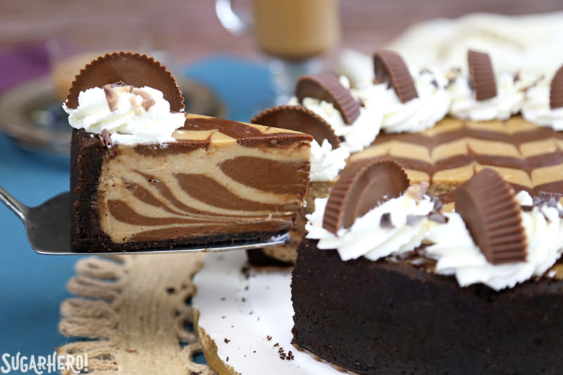 Chocolate Peanut Butter Cheesecake - removing a slice from the whole cake | From SugarHero.com