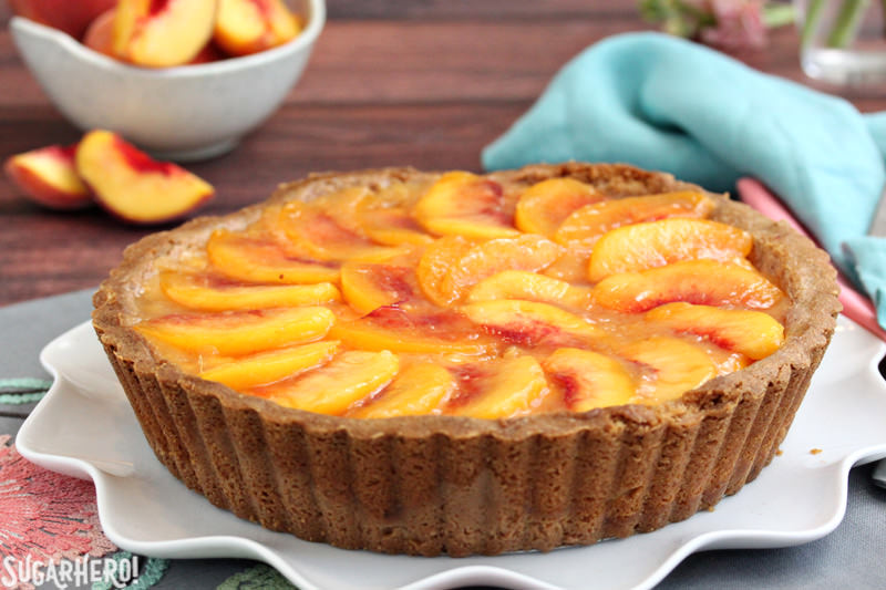 A whole no-bake Fresh Peach Tart on a serving plate | From SugarHero.com