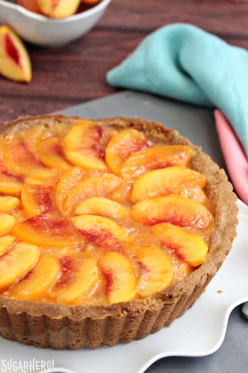 Vertical image of a no-bake Fresh Peach Tart with peaches in the background | From SugarHero.com