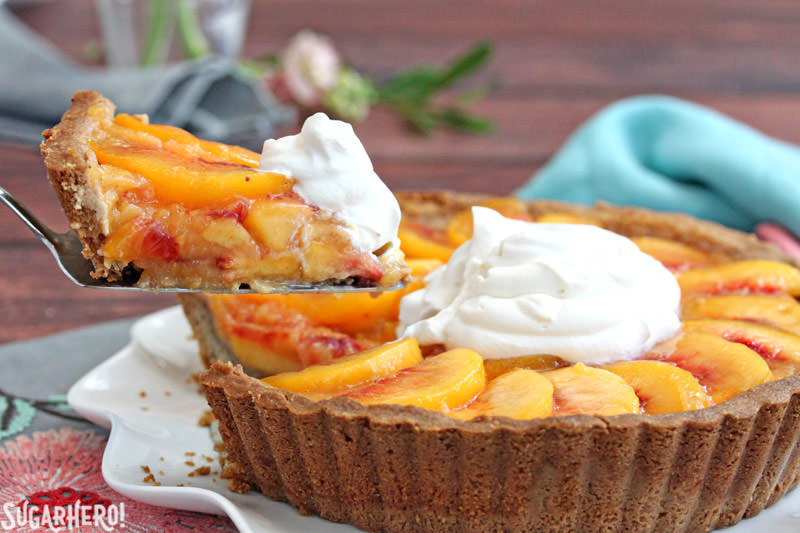 Lifting out a slice of Fresh Peach Tart, a no-bake tart recipe featuring juicy ripe peaches in a buttery shell | From SugarHero.com