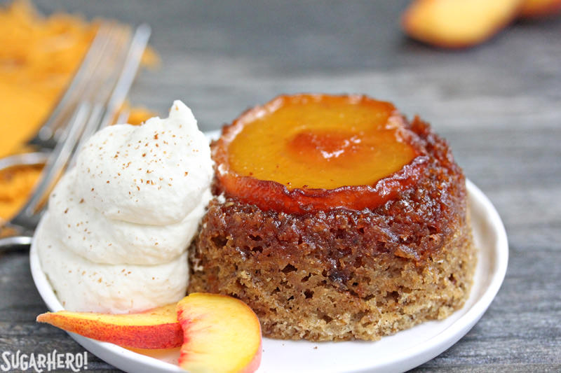 Close-up of Peach Upside-Down Cakes on a plate with whipped cream and fresh peach slices | From SugarHero.com