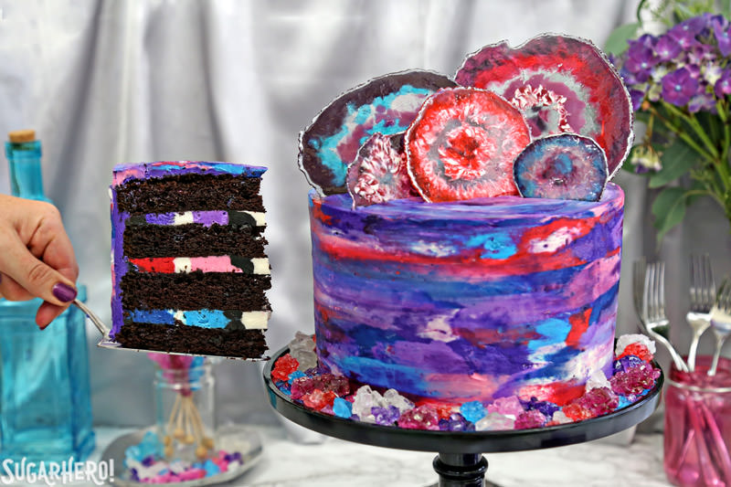 Removing a slice of chocolate cake from the side of a fully decorated agate cake, with a watercolor buttercream effect and candy agate slices on top | From SugarHero.com