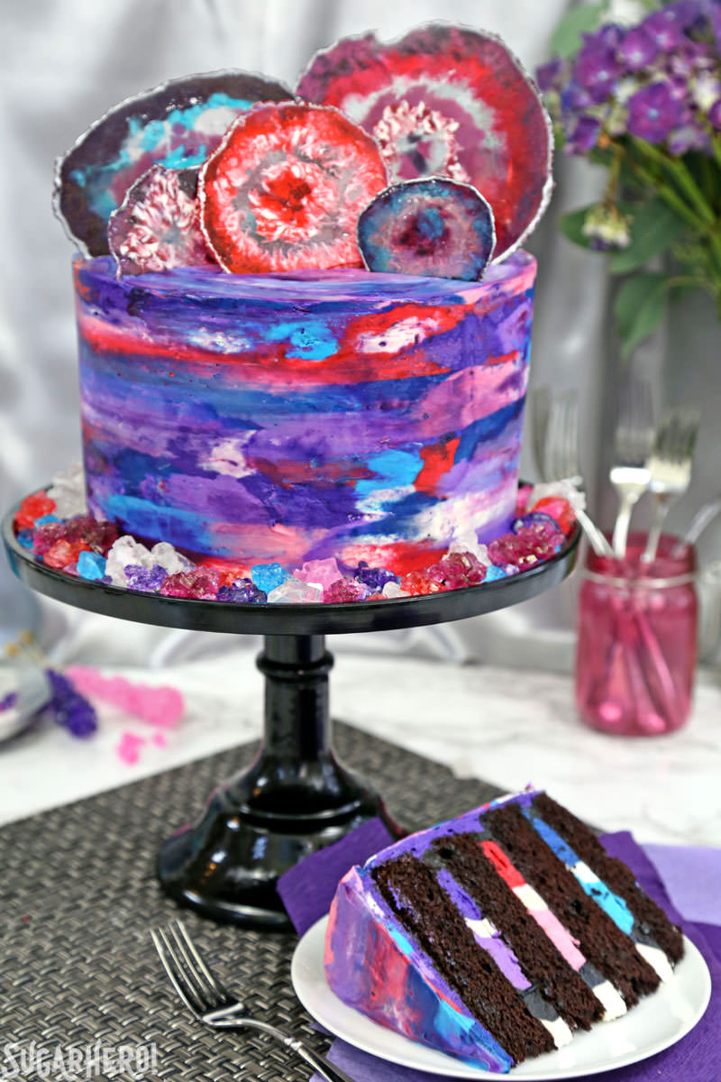 Agate Cake - chocolate cake with watercolor buttercream and candy agate slices on top, with a slice taken out | From SugarHero.com