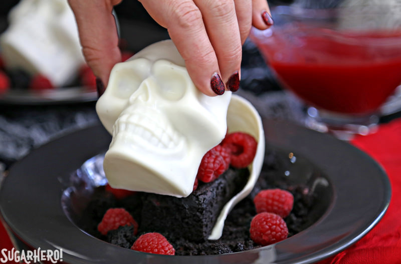 Melting Chocolate Skulls – hand placing the top skull on top of the base | From SugarHero.com