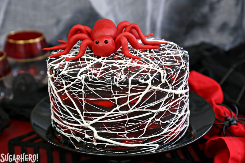 Red Velvet Marshmallow Spiderweb Cake with red candy spider on top | From SugarHero.com