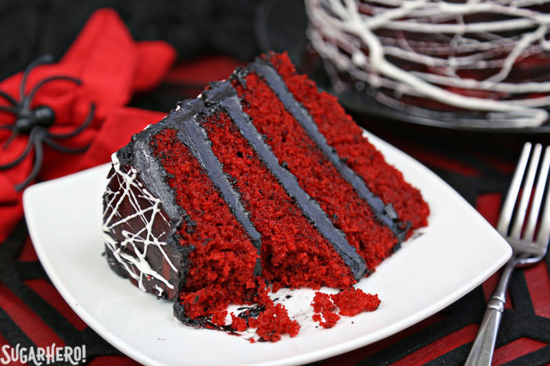 Red Velvet Marshmallow Spiderweb Cake - single slice with bite taken out of it | From SugarHero.com