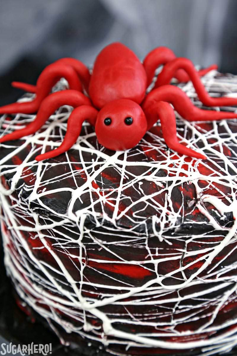 Red Velvet Marshmallow Spiderweb Cake - red candy spider on top of marshmallow web-covered cake | From SugarHero.com