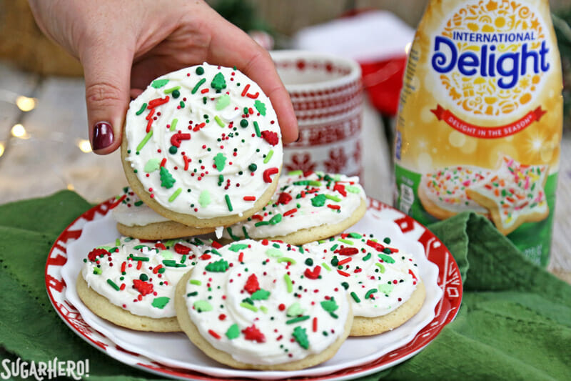 Big Soft Sugar Cookies - sugar cookies arranged on a plate, with a hand reaching for the cookie on top | From SugarHero.com