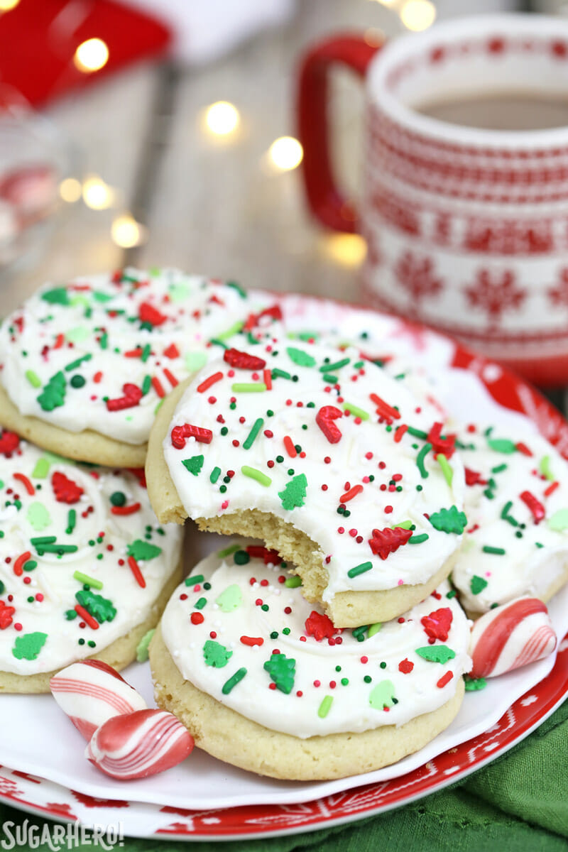 Big Soft Sugar Cookies - cookies arranged on a plate, with a bite taken out of the top cookie | From SugarHero.com