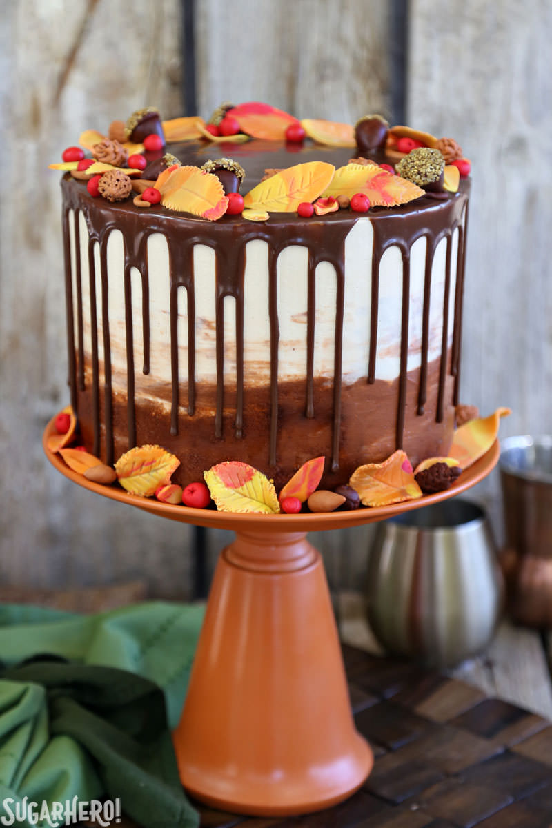 Festive Fall Layer Cake – a beautiful autumn cake! It's a moist chocolate cake with a caramel-pecan filling, decorated with chocolate ganache drips and gorgeous, edible fall decorations! | From SugarHero.com