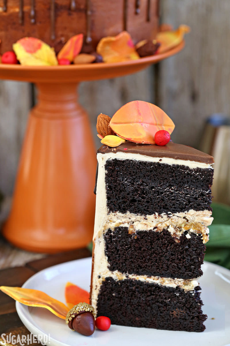 Festive Fall Layer Cake – close-up of cake slice with cake on stand in background | From SugarHero.com