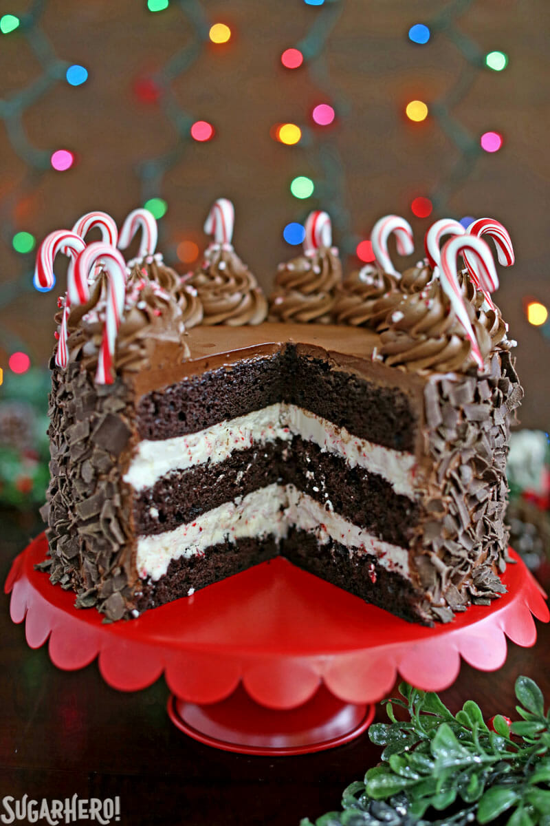 Chocolate Candy Cane Cake – the cake cut open on a red cake stand | From SugarHero.com