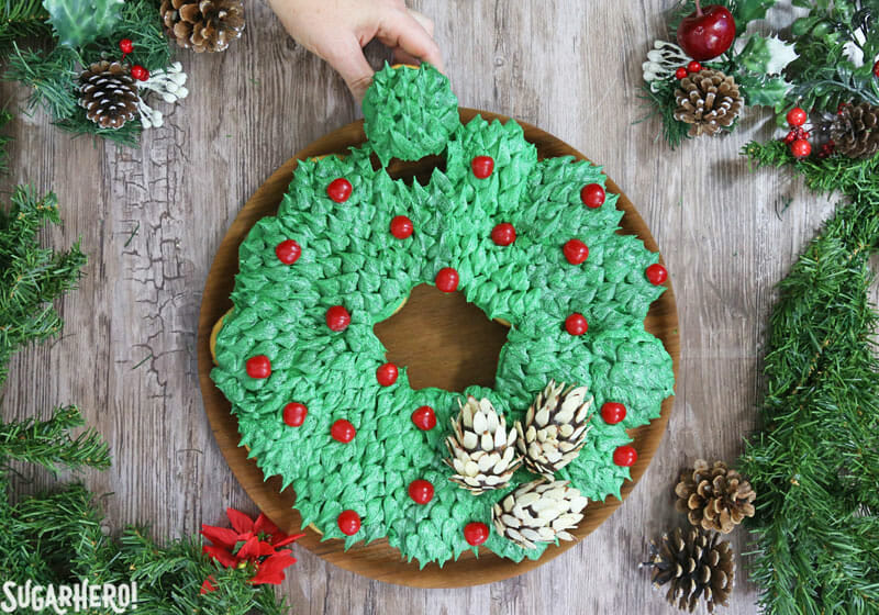 Pull-Apart Cupcake Wreath Cake - picture of hand removing a cupcake from the cupcake wreath. | From SugarHero.com