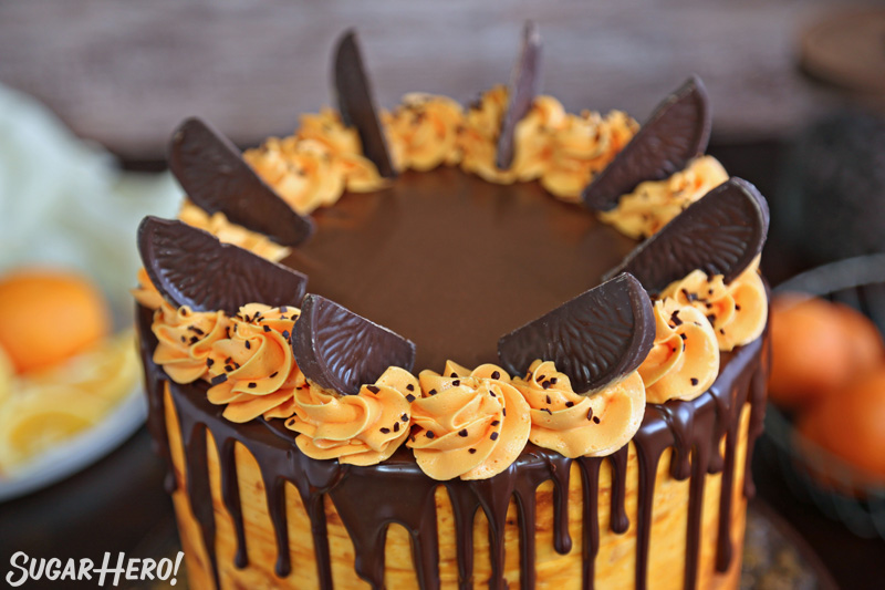 Chocolate Orange Cake - close-up of the top of the cake, with orange frosting rosettes and chocolate orange slices for decoration | From SugarHero.com