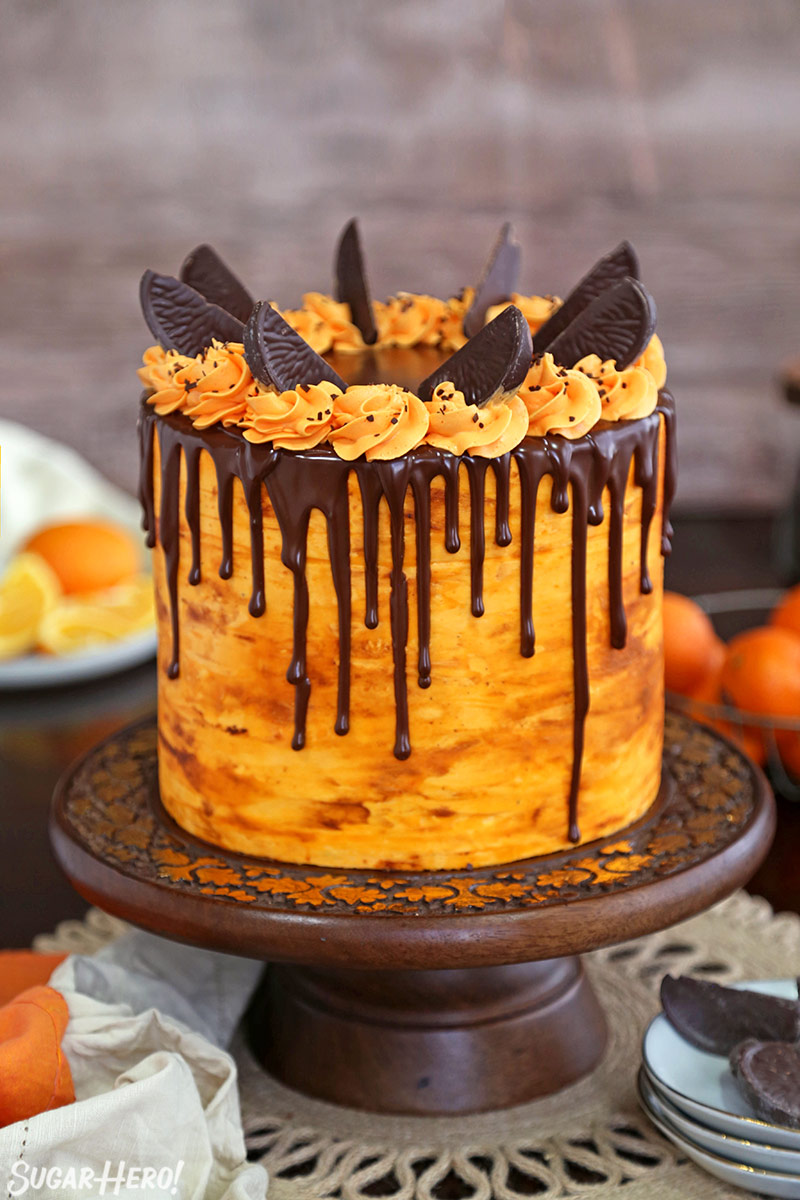 Chocolate-Orange Cake - tall chocolate cake frosted with orange buttercream and a drippy chocolate glaze | From SugarHero.com