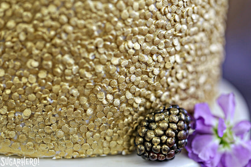 Gold Sequin Watercolor Cake - close-up of edible gold sequins on cake | From SugarHero.com