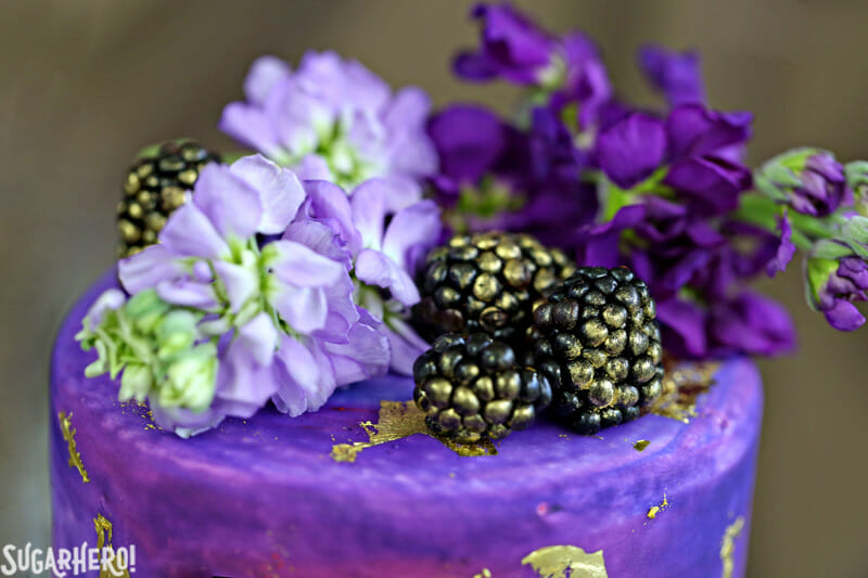 Gold Sequin Watercolor Cake - close-up of the cake topper made with fresh flowers and blackberries | From SugarHero.com