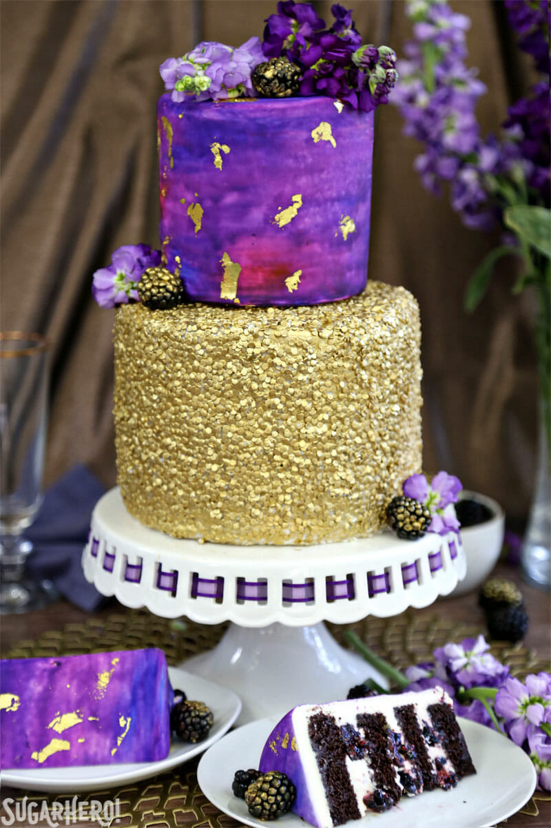 Gold Sequin Watercolor Cake - picture of the full cake on a cake stand with several slices scattered around it | From SugarHero.com
