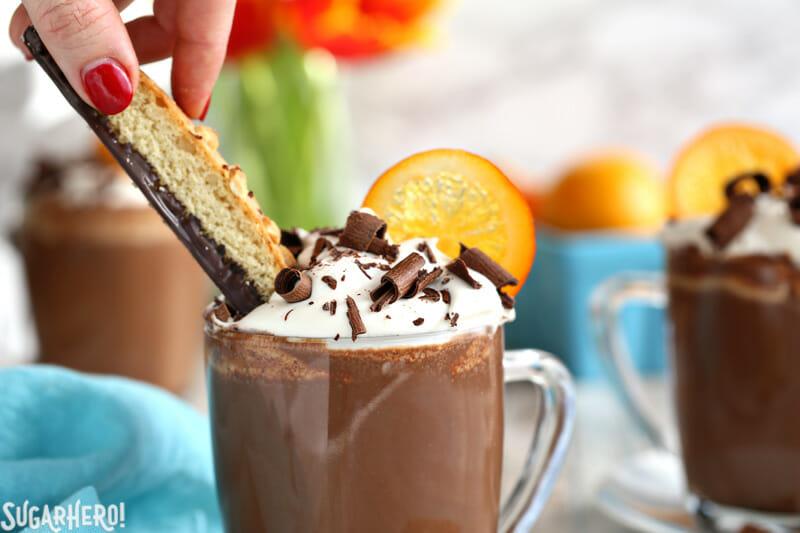 Hand dipping chocolate biscotti into a mug of Orange Hot Chocolate | From SugarHero.com