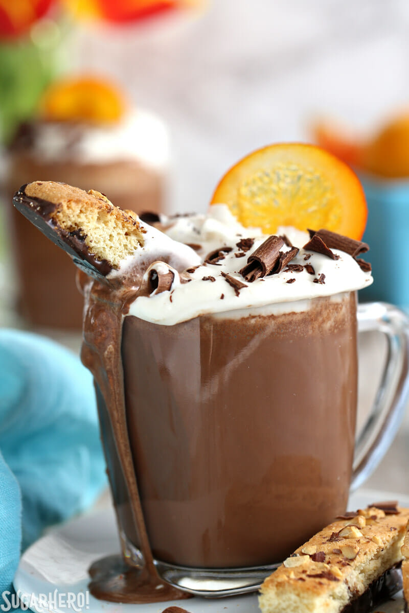 Close-up of biscotti in a mug of Orange Hot Chocolate with hot chocolate flowing down the side | From SugarHero.com