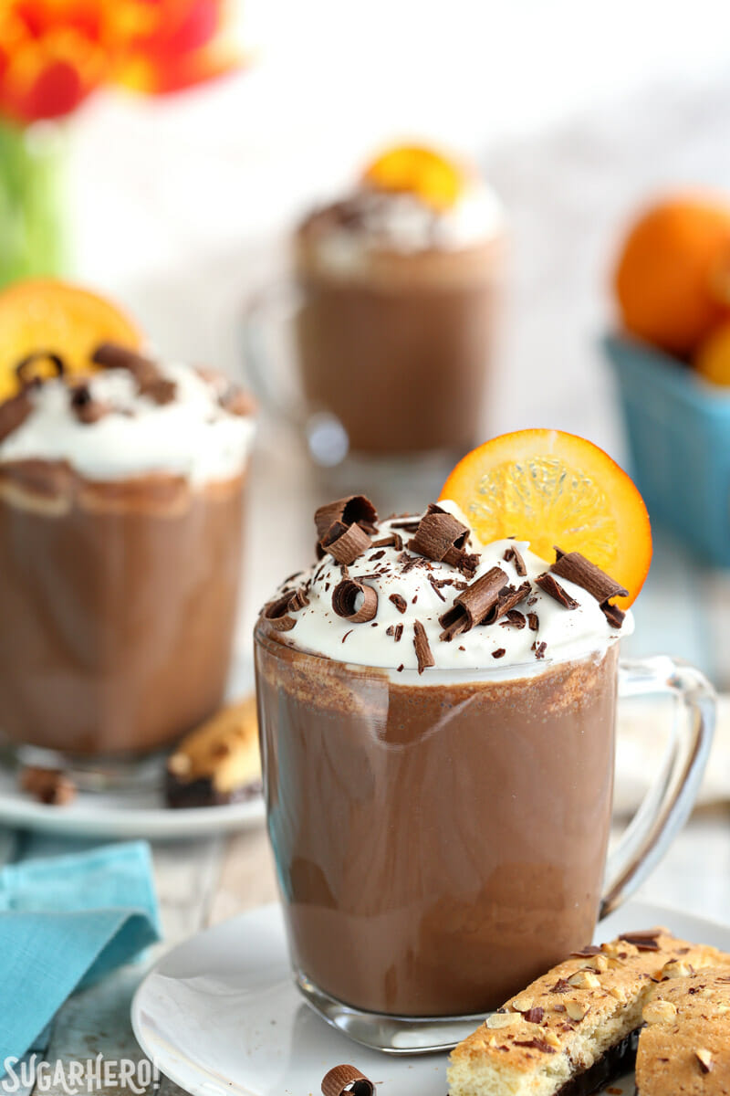 Orange Hot Chocolate mugs topped with whipped cream, chocolate curls, and a candied orange slice | From SugarHero.com