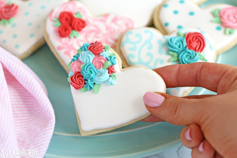 Valentine's Day Sugar Cookies - close-up of hand holding a sugar cookie decorated with royal icing for Valentine's Day | From SugarHero.com