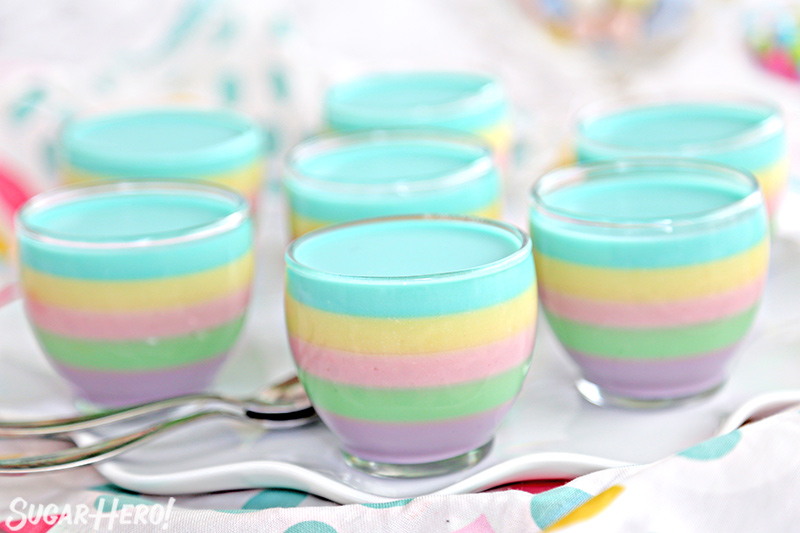 A group of gelatin cups without whipped cream on top, on a white platter.