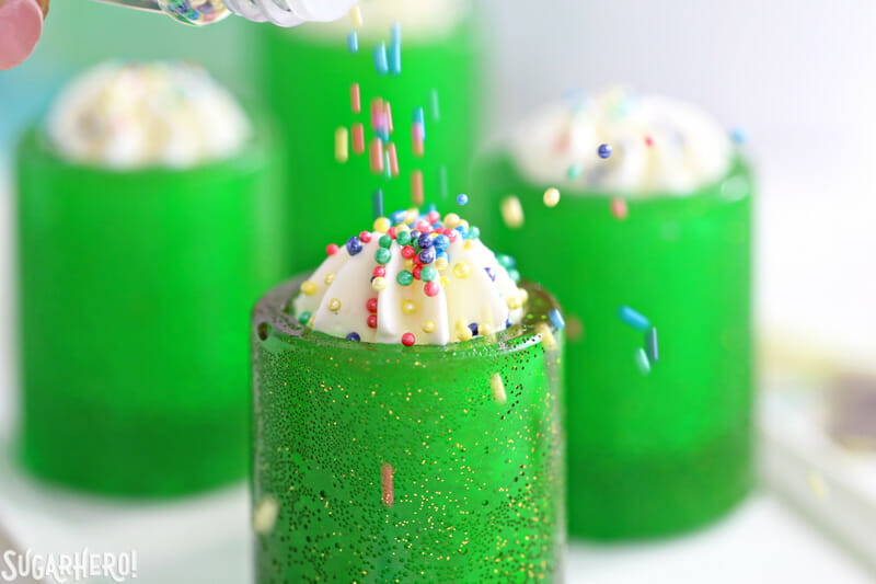 DIY Candy Shot Glasses - pouring sprinkles on top of whipped cream in a candy shot glass | From SugarHero.com
