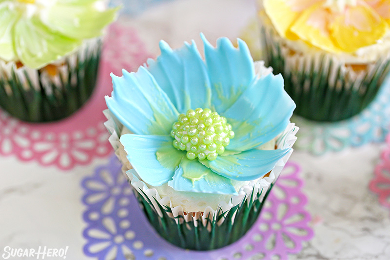 Easy Chocolate Flower Cupcakes - close-up of lemon-coconut cupcake with blue chocolate flower | From SugarHero.com