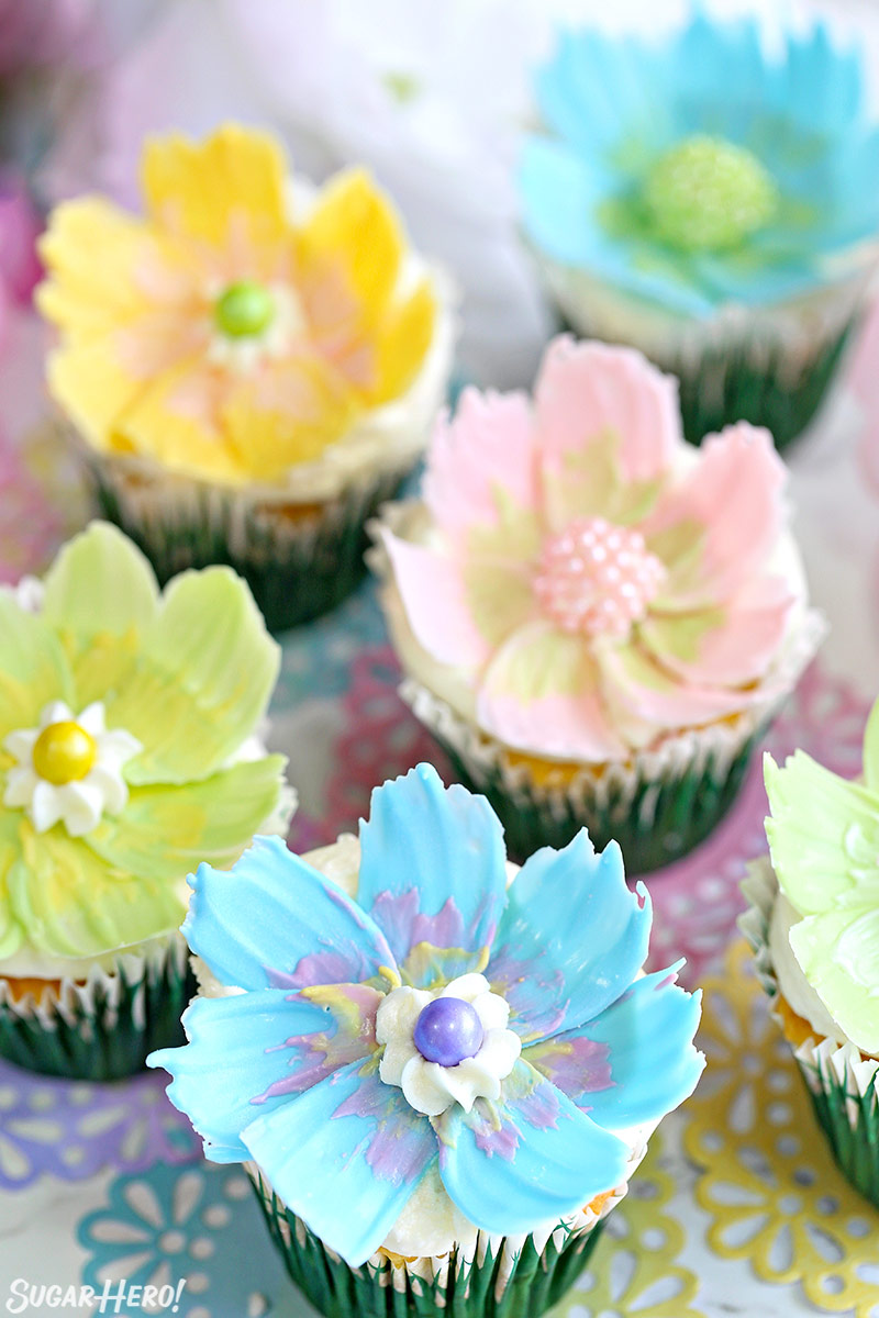 Easy Chocolate Flower Cupcakes - a group of lemon-coconut cupcakes with edible chocolate flowers on top | From SugarHero.com