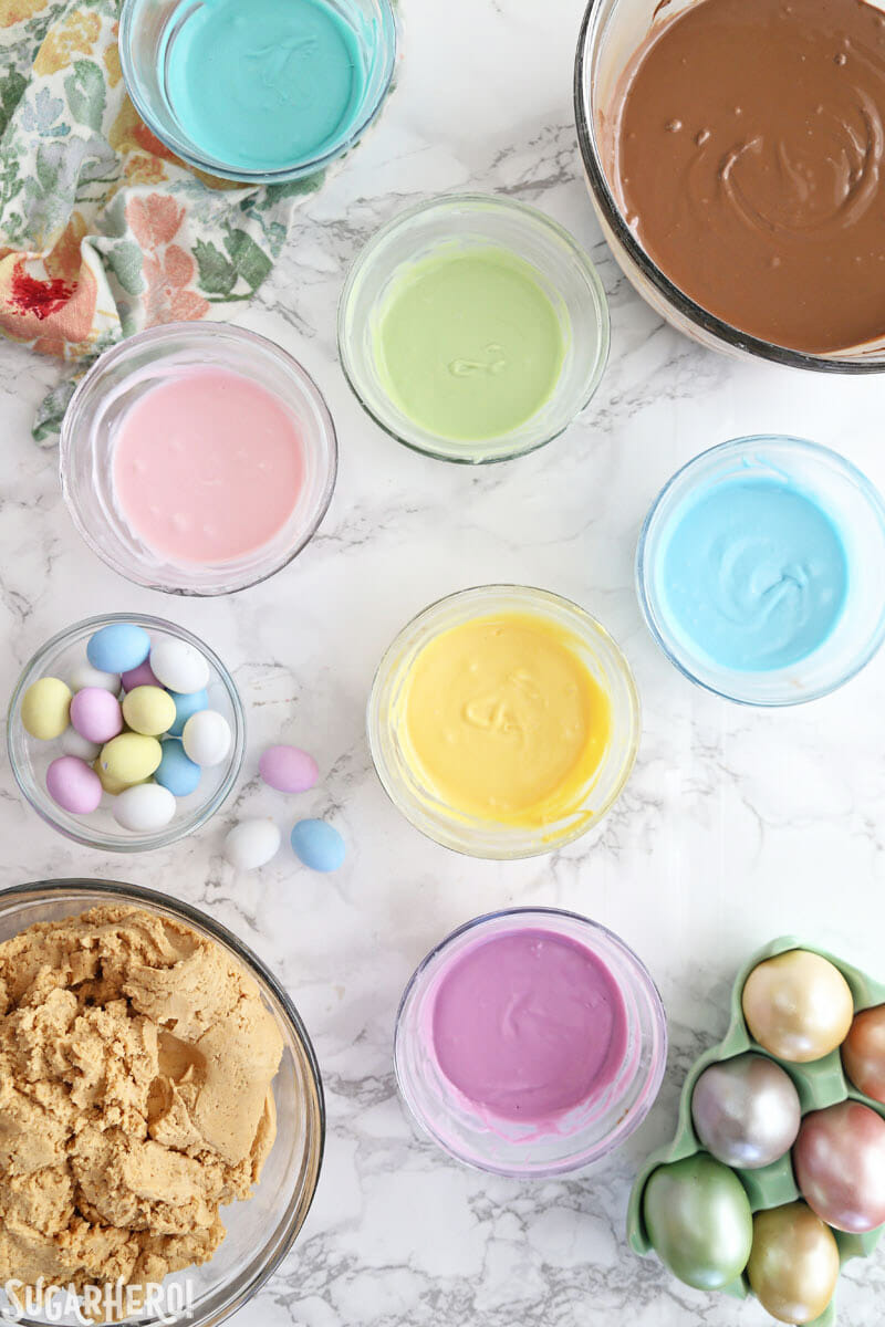 Peanut Butter Easter Eggs - overhead shot of peanut butter egg components, including colored candy coating, chocolate coating, and peanut butter filling   From SugarHero.com