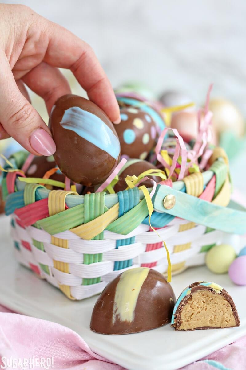 Peanut Butter Easter Eggs - hand picking up a peanut butter egg from an Easter basket | From SugarHero.com