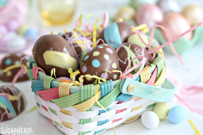 Peanut Butter Easter Eggs - colorful Easter basket full of pastel grass and peanut butter eggs coming out of the top | From SugarHero.com