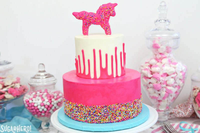 Circus Animal Layer Cake - pink sprinkled cake on bottom, white ganache drip cake on top | From SugarHero.com