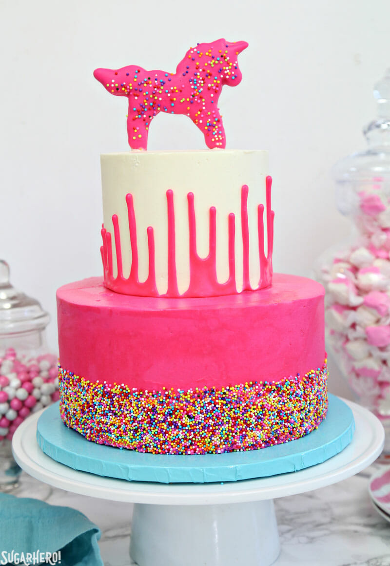 Circus Animal Layer Cake - two-layered cake with a pink sprinkled base layer and white cake decorated with an upside-down ganache drip | From SugarHero.com
