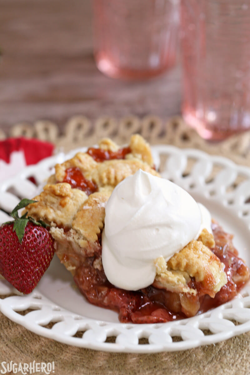 Strawberry Rhubarb Pie - single slice on a plate with whipped cream on top | From SugarHero.com