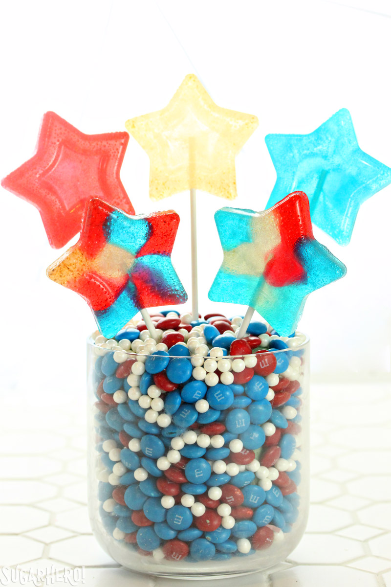 Easy Homemade Lollipops - red, white, and blue star-shaped homemade lollipops in candy vase | From SugarHero.com