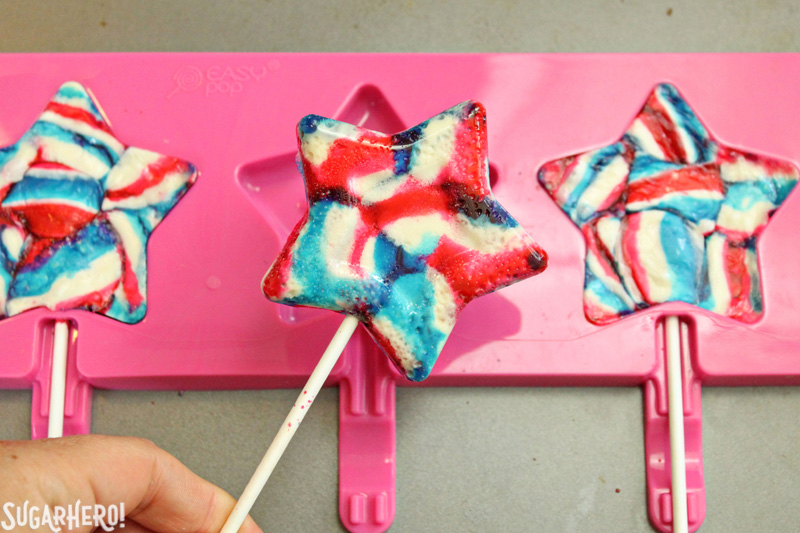 Easy Homemade Lollipops - swirled red, white, and blue star-shaped lollipop | From SugarHero.com