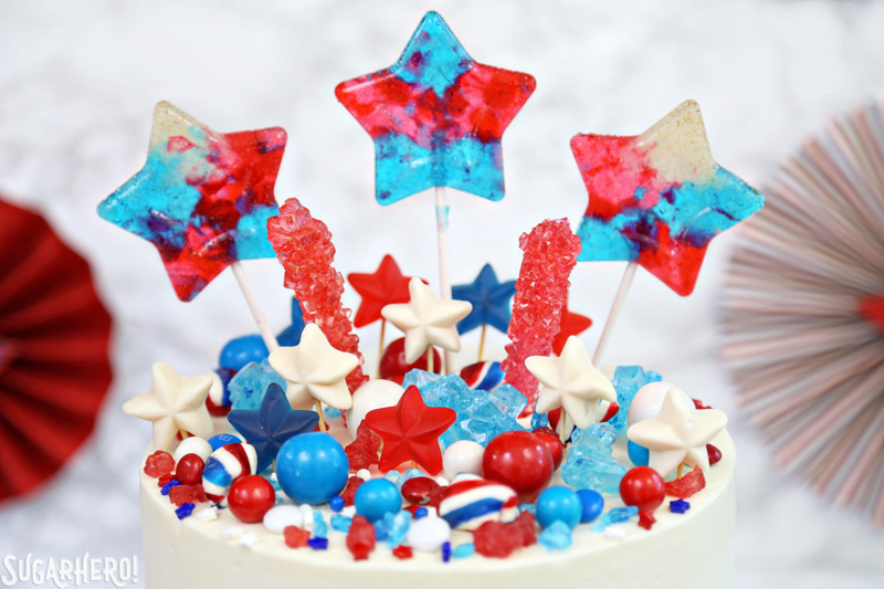 Fourth of July Layer Cake - close-up of colorful candy assortment on top of tall layer cake | From SugarHero.com