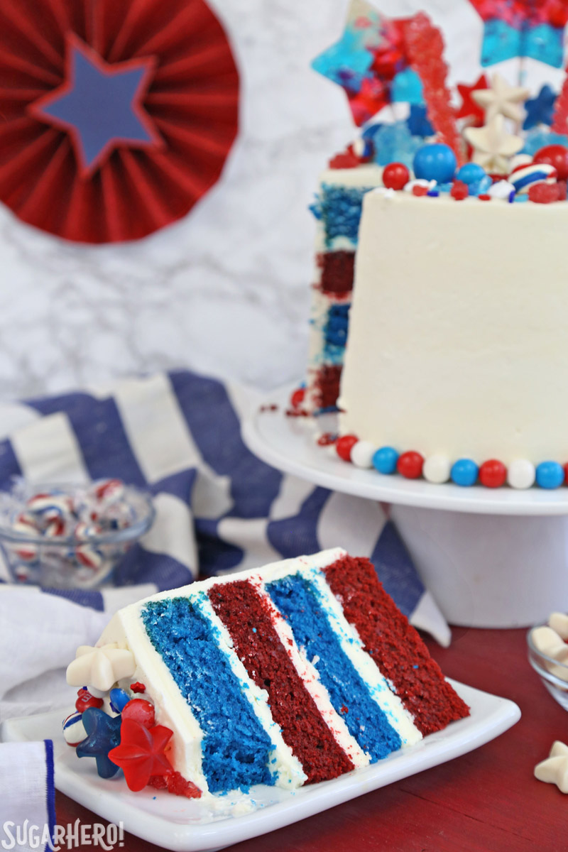 Fourth of July Layer Cake - slice of red and blue velvet cake displayed in front of a tall layer cake | From SugarHero.com