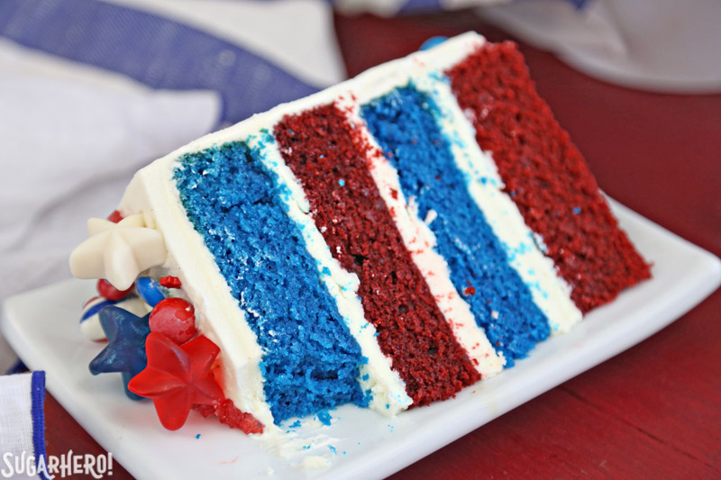 Fourth of July Layer Cake - close-up of slice of red and blue velvet cake with a bite taken out of it | From SugarHero.com