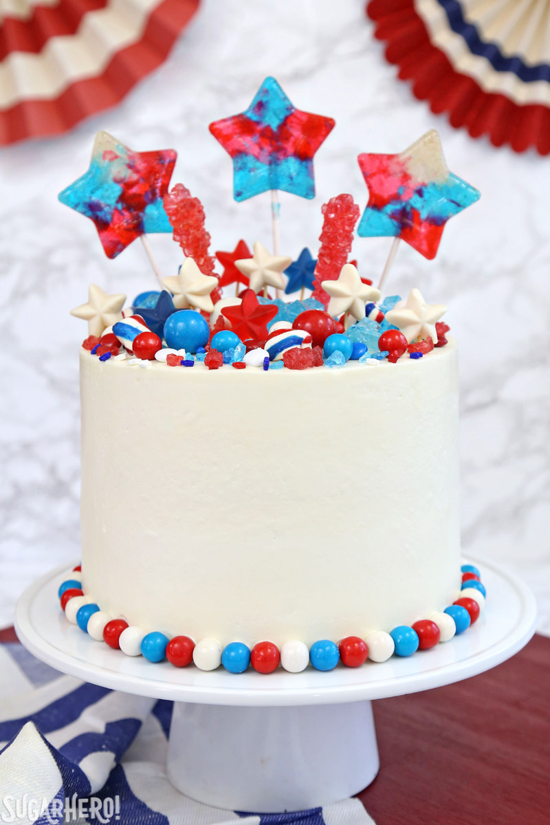 Fourth of July Layer Cake - tall layer cake with red, white, and blue candies on top | From SugarHero.com